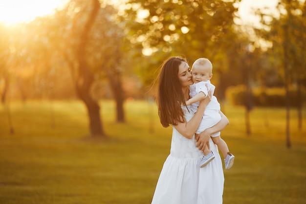 Mooie jonge vrouw in een lange witte jurk met een schattige kleine babyjongen in shirt en korte broek op haar handen poseren in de groene tuin in zonnige zomerdag