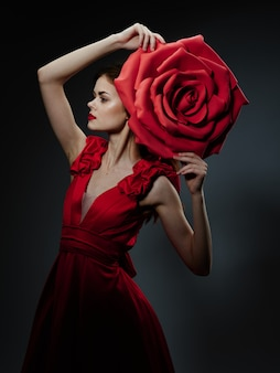 Mooie jonge vrouw in een luxe jurk met rozen, rozenblaadjes