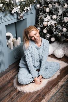 Mooie jonge vrouw in een modieus gebreid blauw pak met blond haar met schattige glimlach poseren in een kamer met een kerstboom