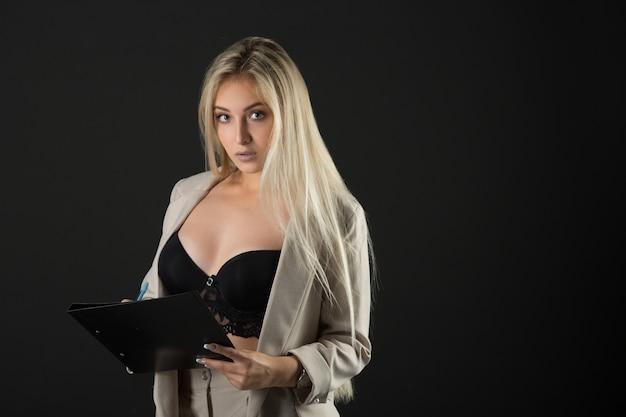 Mooie jonge vrouw in een pak en sexy lingerie, met een map en een pen in handen