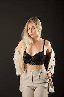 Mooie jonge vrouw in een pak en sexy lingerie