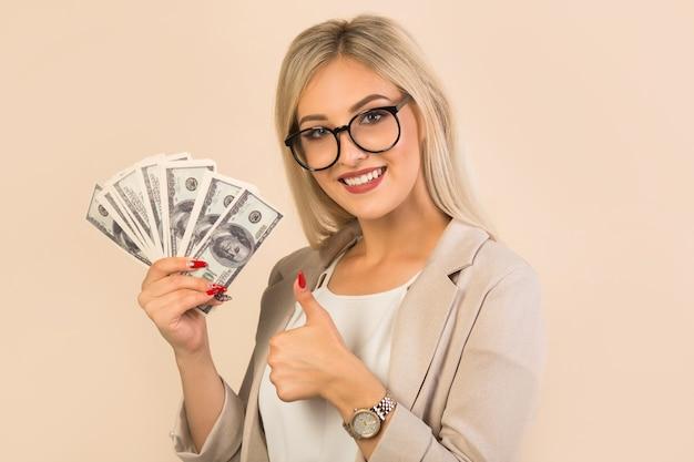 Mooie jonge vrouw in een pak op beige met dollars in de hand