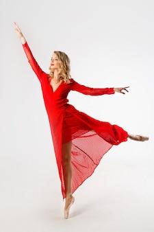 Mooie jonge vrouw in een rode jurk in een ballet-pose op een witte achtergrond