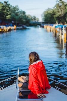 Mooie jonge vrouw in een rode regenjas rijdt een prive-jacht. stockholm, zweden