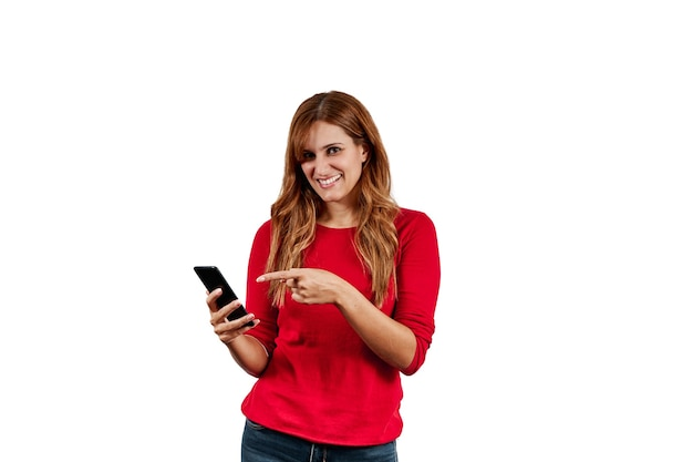 Mooie jonge vrouw in een rode trui, wijzend op het scherm van haar telefoon, geïsoleerd op een witte achtergrond.