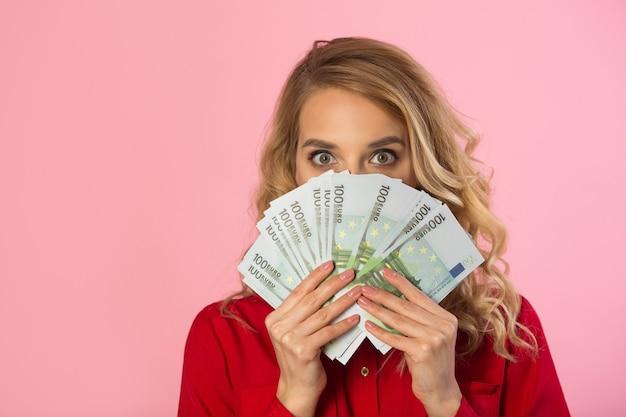 Mooie jonge vrouw in een rood shirt met euro's in handen op een roze muur met een verbaasd gezicht