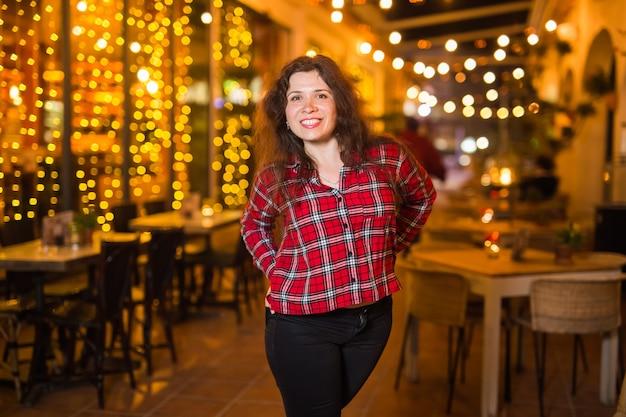 Mooie jonge vrouw in een rood shirt op een achtergrond van een nachtstad