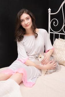 Mooie jonge vrouw in een slapende jurk zittend op een bed en streelt een bleke kat.