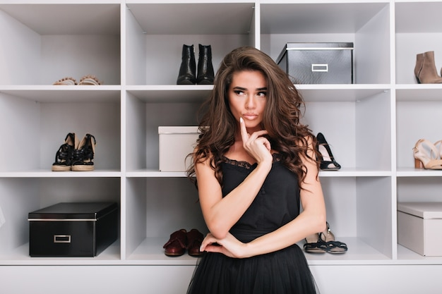 Mooie jonge vrouw in een stijlvolle kledingkast en denkt wat ze moet dragen. ze is boos over de kledingkeuze. plaats voor tekst.
