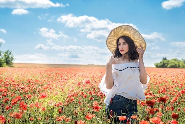 Mooie jonge vrouw in een strooien hoed op een papavergebied in de zomer