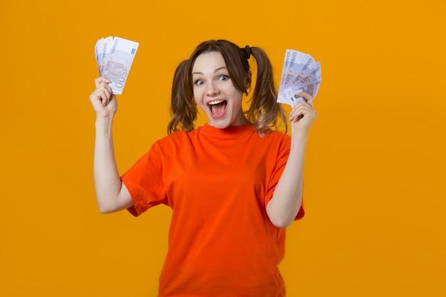 Mooie jonge vrouw in een t-shirt met euro in handen