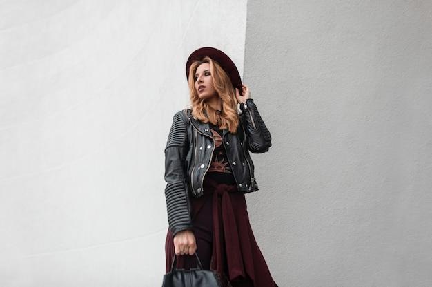 Mooie jonge vrouw in een trendy hoed in een stijlvolle zonnebril in een vintage leren jas met een rugzak