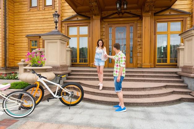 Mooie jonge vrouw in een trendy outfit die op de trap buiten een luxe huis staat en haar vriendje begroet
