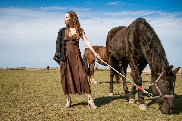 Mooie jonge vrouw in een veld met paarden. aantrekkelijk fotomodel.