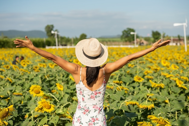 Mooie jonge vrouw in een veld met zonnebloemen in een witte jurk. reizen op het weekend-concept. portret van authentieke vrouw in strohoed. buiten op het zonnebloemveld.