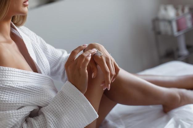 Mooie jonge vrouw in een wit gewaad past vochtinbrengende crème toe op haar handen, zittend op een bank in een schoonheidssalon. spa.