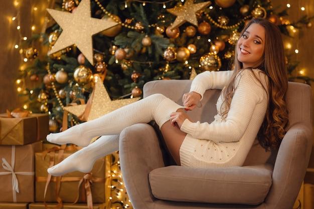 Mooie jonge vrouw in een witte gebreide jurk en kousen in de buurt van een mooie kerstboom in gouden sieraden. het idee en concept van een gelukkig kerstfeest en nieuwjaar