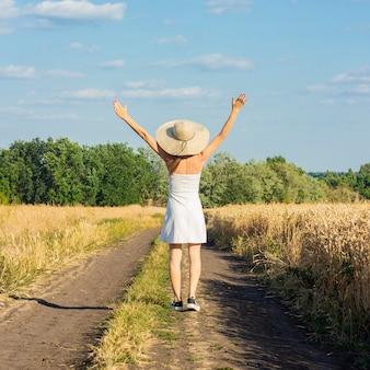 Mooie jonge vrouw in een witte jurk en hoed loopt langs de weg tussen twee velden met tarwe