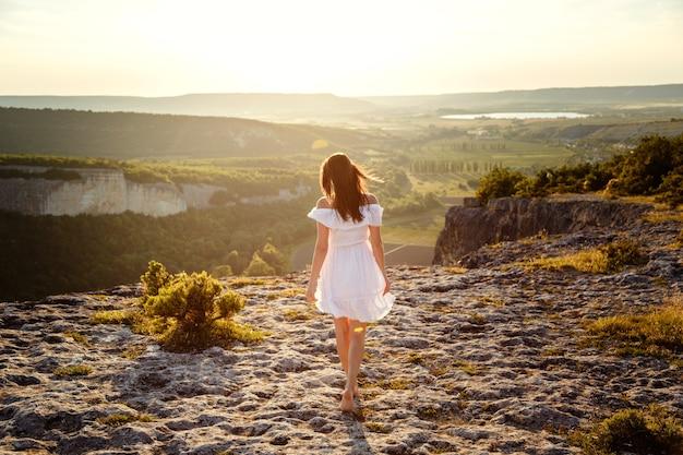 Mooie jonge vrouw in een witte jurk geniet van een prachtig landschap in de bergen tijdens zonsondergang