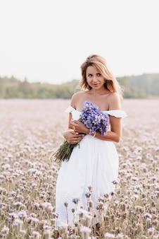 Mooie jonge vrouw in een witte jurk met een boeket bloemen in een veld in de zomer in de natuur
