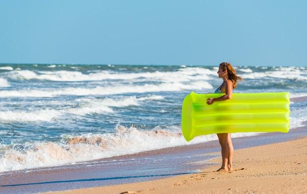 Mooie jonge vrouw in een zwembroek loopt langs het strand met een luchtbed in haar handen