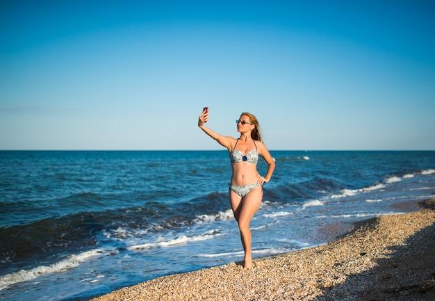 Mooie jonge vrouw in een zwembroek maakt selfie op een smartphone terwijl u ontspant op het strand aan zee op een zonnige warme zomerdag