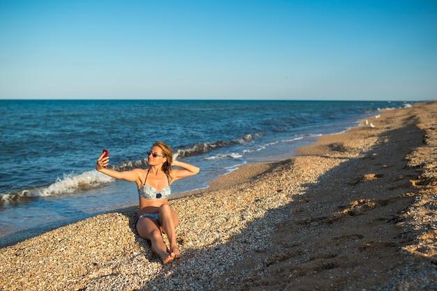 Mooie jonge vrouw in een zwembroek maakt selfie op een smartphone terwijl u ontspant op het strand