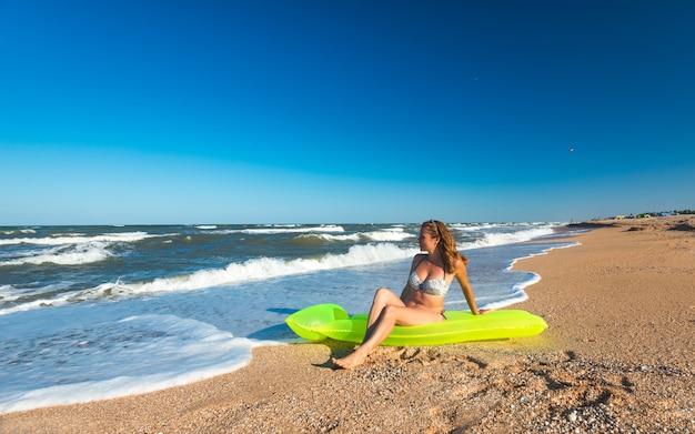 Mooie jonge vrouw in een zwembroek zit op een luchtbed aan een zandstrand op een zonnige warme zomerdag