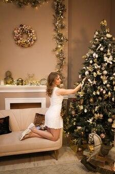 Mooie jonge vrouw in elegante jurk siert de boom met speelgoed in een luxe interieur