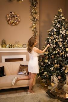 Mooie jonge vrouw in elegante jurk siert een kerstboom in een luxe interieur