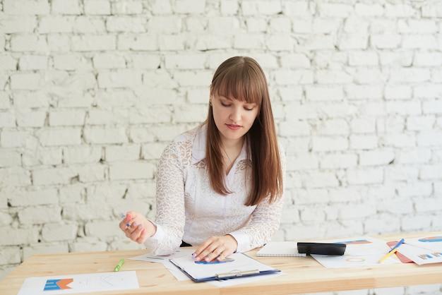 Mooie jonge vrouw in elegante vrijetijdskleding die naar de grafiek kijkt terwijl ze op kantoor staat.