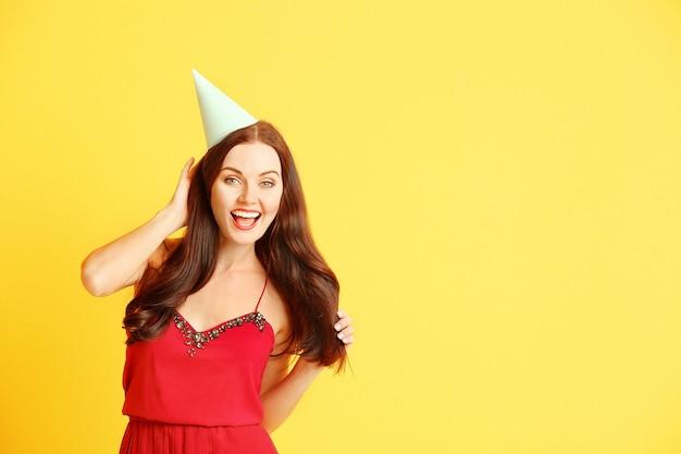 Mooie jonge vrouw in feestmuts op gele achtergrond