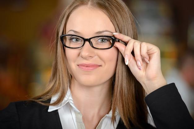 Mooie jonge vrouw in formalwear glazen aanpassen.