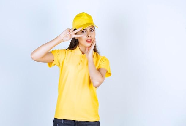 Mooie jonge vrouw in geel t-shirt en pet op zoek poseren op witte achtergrond.