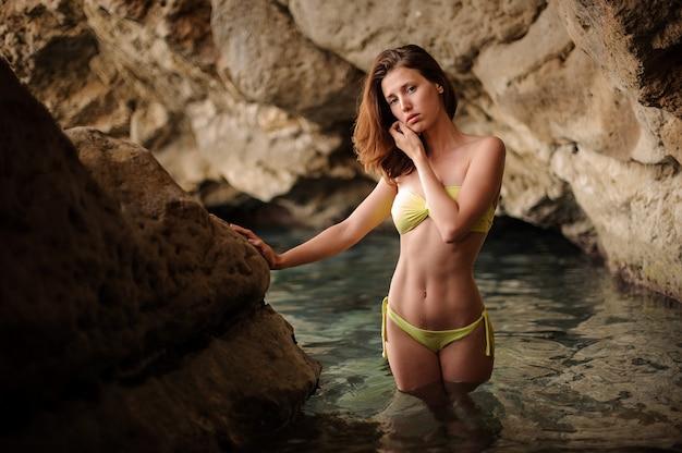 Mooie jonge vrouw in gele bikini die zich in het hol bevindt