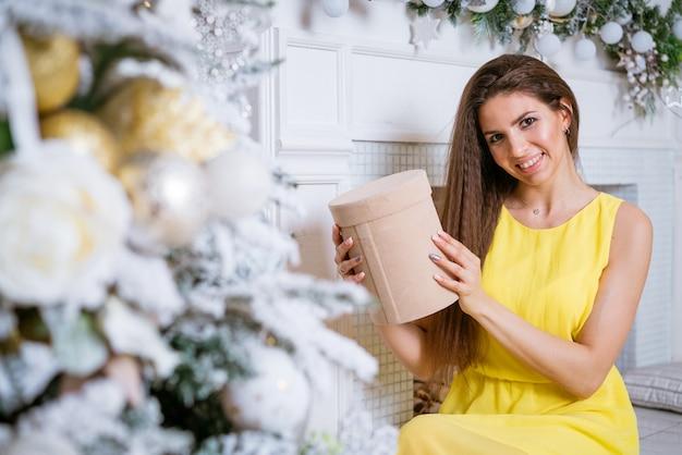Mooie jonge vrouw in gele jurk houdt aanwezig bij feestelijke kerstboom bij de open haard in een ...
