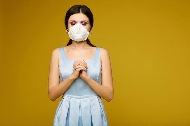 Mooie jonge vrouw, in gezichtsmasker en jurk, met gelede armen en gesloten ogen bidt brunette meisje in geneeskunde masker bidt voor genezing van griepepidemie