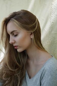 Mooie jonge vrouw in grijze blouse, close-up portret van schattig aantrekkelijk model