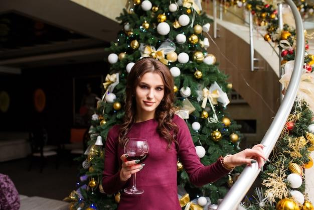 Mooie jonge vrouw in grijze jurk staat met wijnglas in haar handen