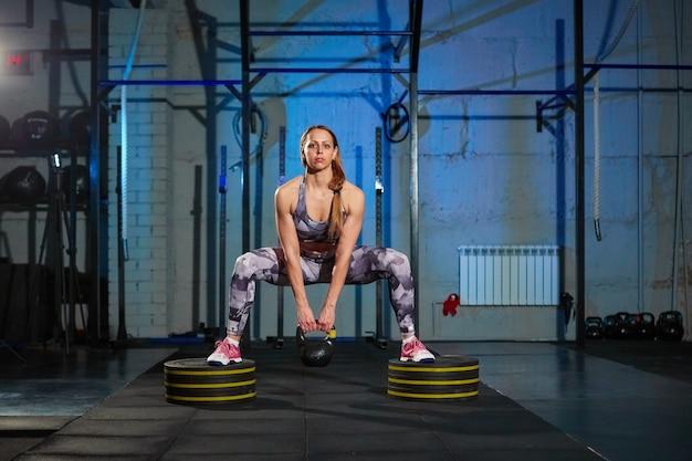 Mooie jonge vrouw in grijze sportkleding die oefening met gewicht doet