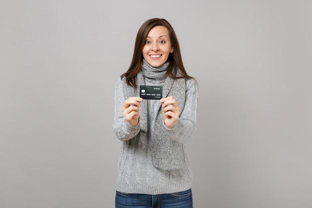 Mooie jonge vrouw in grijze trui, sjaal houd creditcard geïsoleerd op grijze muur achtergrond in studio. gezonde mode levensstijl mensen oprechte emoties, koude seizoen concept. bespotten kopie ruimte.