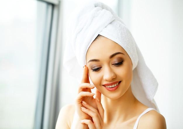 Mooie jonge vrouw in handdoek allemaal klaar om kuur te krijgen. meisje is seksueel poseren