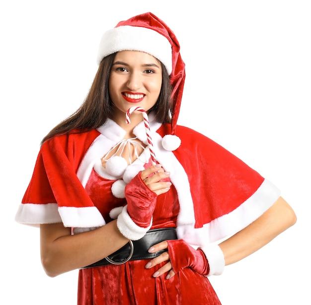 Mooie jonge vrouw in het kostuum van de kerstman en met zuurstok op wit