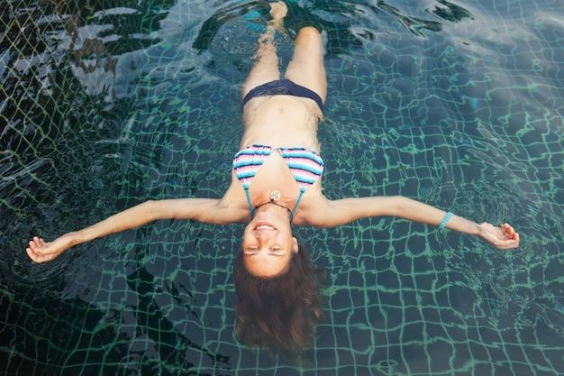 Mooie jonge vrouw in het zwembad, schot van bovenaf