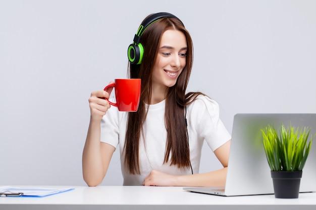 Mooie jonge vrouw in hoofdtelefoons op het werk