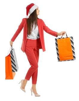 Mooie jonge vrouw in kerstman hoed en met zakken op witte achtergrond. kerstinkopen concept