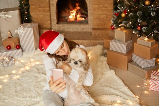Mooie jonge vrouw in kerstmuts en trui met kleine hond knuffels, zittend in feestelijke woonkamer op verdieping bij open haard, dame houdt lippen afgerond wil pekingese puppy kussen.