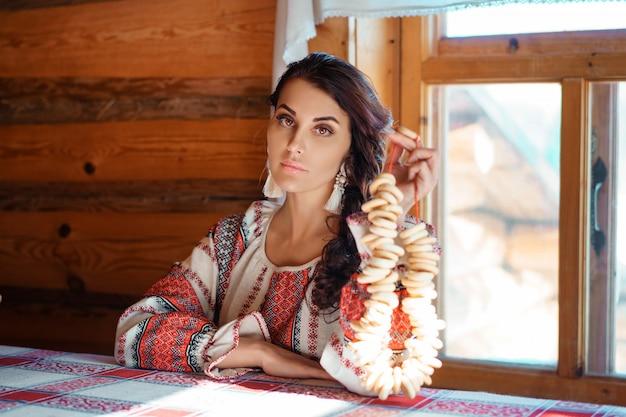 Mooie jonge vrouw in klederdracht zit in een hut
