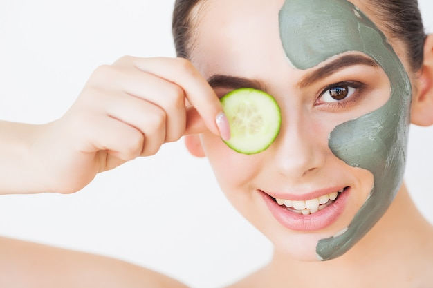 Mooie jonge vrouw in klei modder masker op gezicht die ogen behandelen met plakjes komkommer,