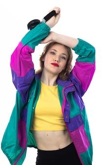 Mooie jonge vrouw in kleurrijke jas en hoofdtelefoon te houden